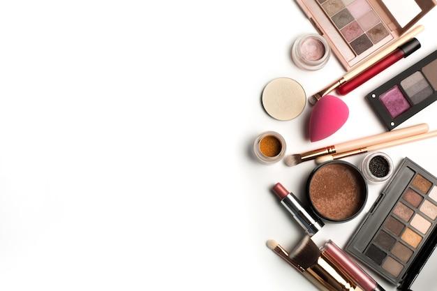 Pose à plat de palettes de maquillage, de pigments de fard à paupières et de brillant à lèvres. espace pour le texte