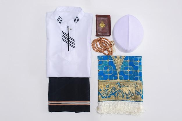 Pose à plat de vêtements traditionnels musulmans et d'accessoires pour prier avec le livre saint al coran et les perles de prière il y a une lettre arabe qui signifie le livre saint