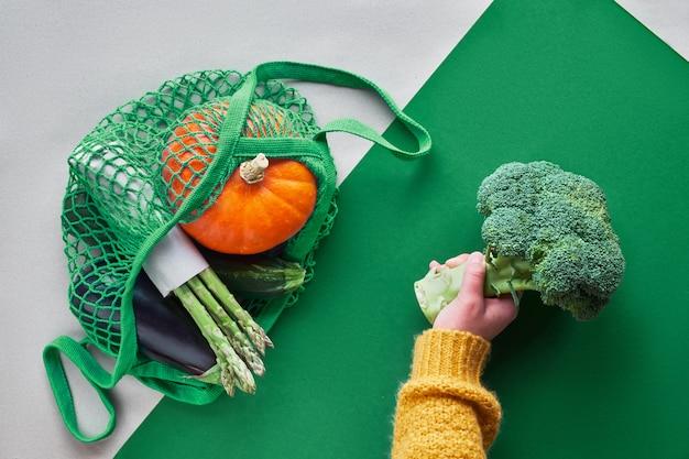 Pose à plat zéro déchet écologique avec les mains tenant le brocoli et le sac de ficelle avec citrouille orange et asperges vertes emballés dans du papier kraft vue de dessus sur papier bicolore marron et vert.