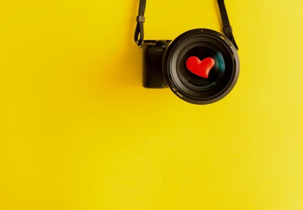 Pose plate d'appareil photo sans miroir avec objectif et coeurs rouges d'amour sur fond jaune