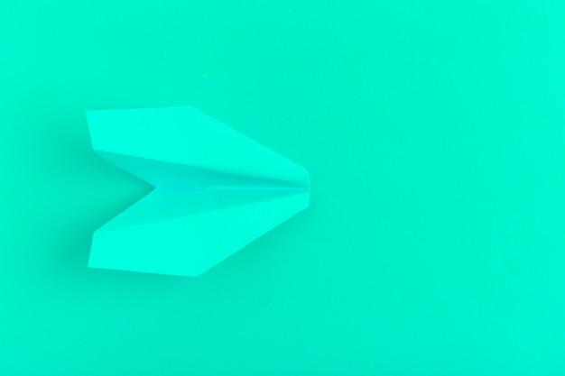 Pose plate d'un avion en papier sur pastel vert