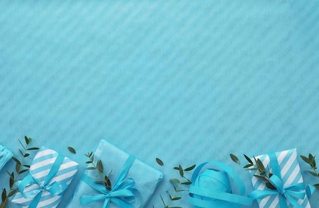 Pose plate avec boîtes-cadeaux emballées et brindilles d'eucalyptus dans des teintes bleu clair