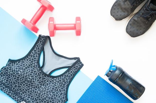 Pose plate créative d'équipements sportifs avec des vêtements de sport sur fond blanc et bleu