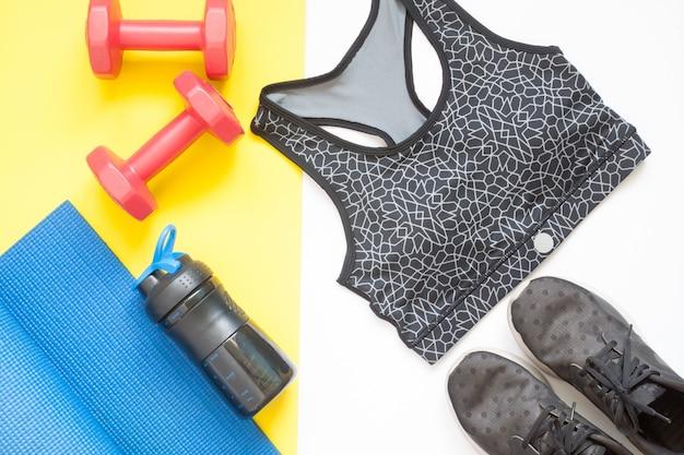 Pose plate créative d'équipements sportifs avec des vêtements de sport sur fond blanc et jaune