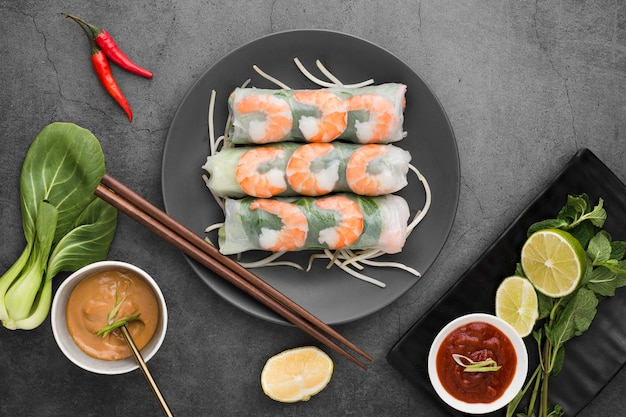 Pose plate de crevettes avec des baguettes et de la sauce