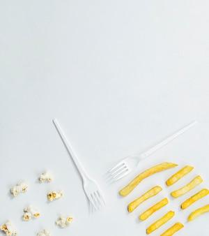 Pose plate de frites avec du maïs soufflé et des fourchettes