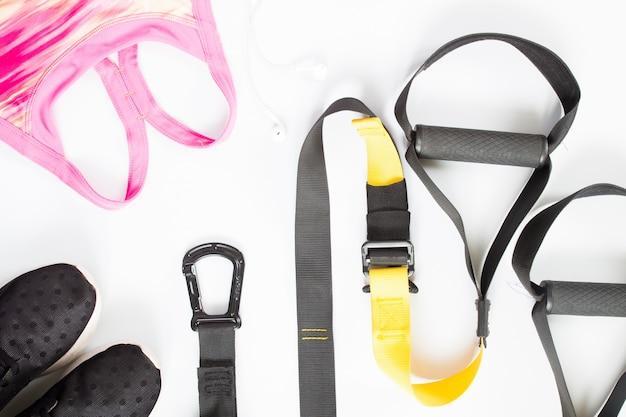Pose plate de matériel de sport, soutien-gorge de sport rose, baskets sur fond blanc. vêtements de sport, vue de dessus