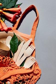 Pose plate de papier artisanal écologique et de vaisselle en bois, lumière dure, zéro déchet, vie sans plastique et respectueuse de l'environnement, gobelets en papier, vaisselle, sac, assiettes et couverts en bois dans un sac en filet de coton