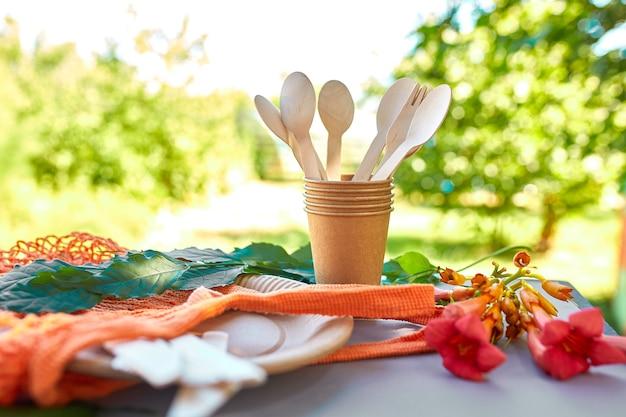 Pose plate de papier artisanal écologique et de vaisselle en bois, zéro déchet, vie sans plastique et respectueuse de l'environnement, gobelets en papier, vaisselle, sac, assiettes et couverts en bois dans un sac en filet de coton