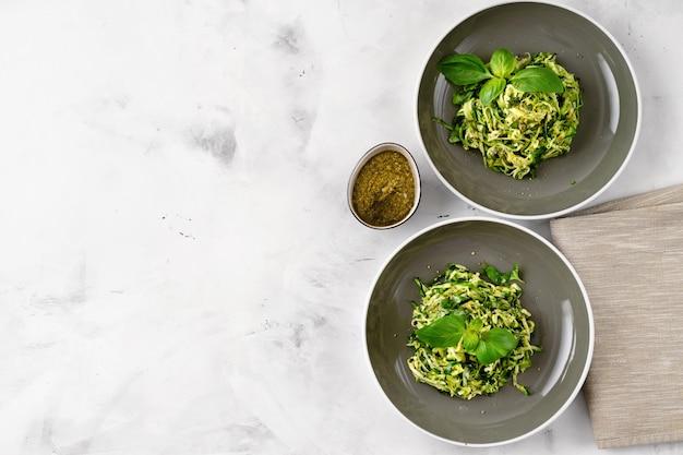 Pose plate de pâtes végétaliennes aux courgettes dans deux assiettes sur fond blanc