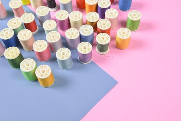 Pose plate de rouleaux de fil de couleur pour coudre sur un fond bicolore