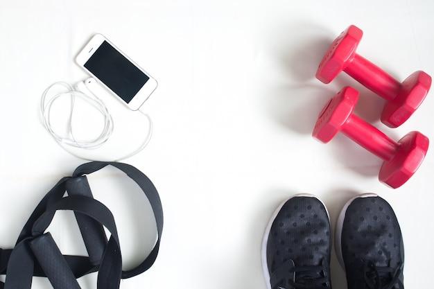 Pose plate de téléphone cellulaire, haltères rouges et équipement de sport sur fond blanc. vêtements de sport, sport, accessoires de sport, équipement sportif, vue de dessus