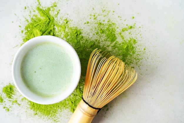 Pose plate de thé vert biologique matcha en poudre avec des outils japonais, un fouet en bambou chasen