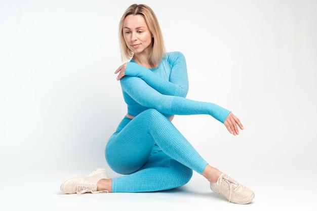 Pose souple. vue sur toute la longueur de la femme blonde assise sur le sol et regardant vers le bas tout en posant sur le fond du mur blanc