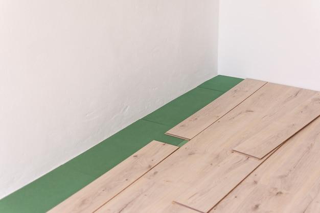 Pose stratifié dans la pièce, feuilles écologiques sous sol et stratifié ou parquet