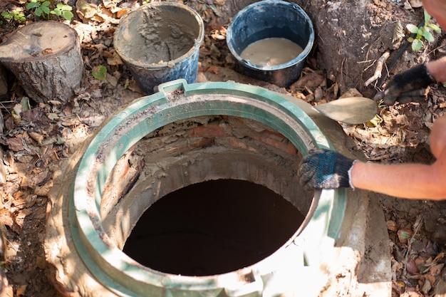 Pose d'une trappe sur un puits d'égout. l'homme renforce le col de la fosse septique.