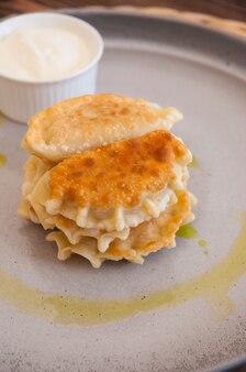 Posekunchiki ou posokunchiki avec crème sure sur une plaque grise dans un restaurant