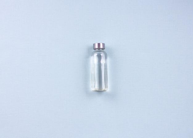 Poser une bouteille d'eau singl sur fond bleu. concept de perte de poids. vue de dessus.
