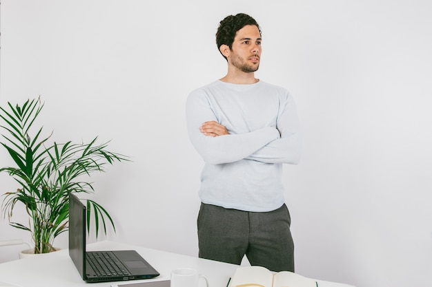 Poser dans le bureau avec les bras croisés