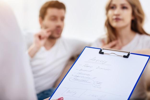 Poser un diagnostic. gros plan des notes d'un psychologue professionnel au cours de la session psychologique avec un jeune couple