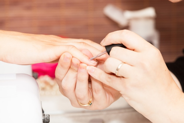 Poser du vernis à ongles sur les mains d'une femme