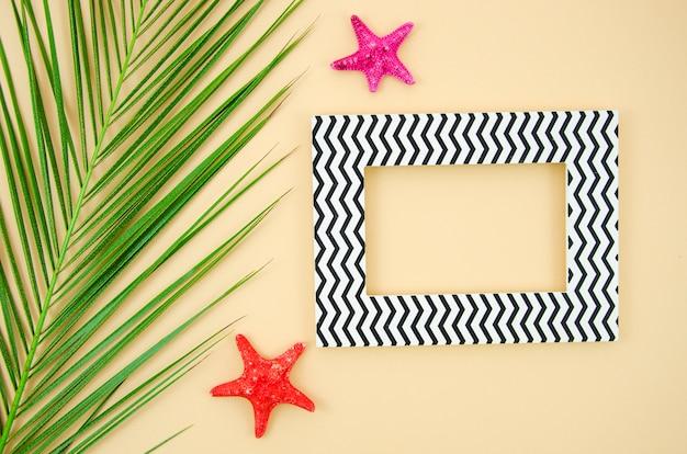 Poser à plat avec une étoile de mer et une feuille de palmier