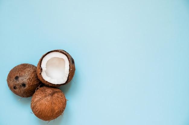 Poser à plat avec des noix de coco mûres sur bleu
