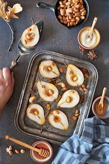 Poser à plat avec un plateau de poires cuites au four avec des noix caramélisées sur du bois foncé