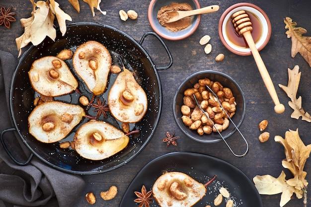 Poser à plat avec un plateau de poires cuites au four avec des noix caramélisées sur une table en bois sombre avec des feuilles d'automne