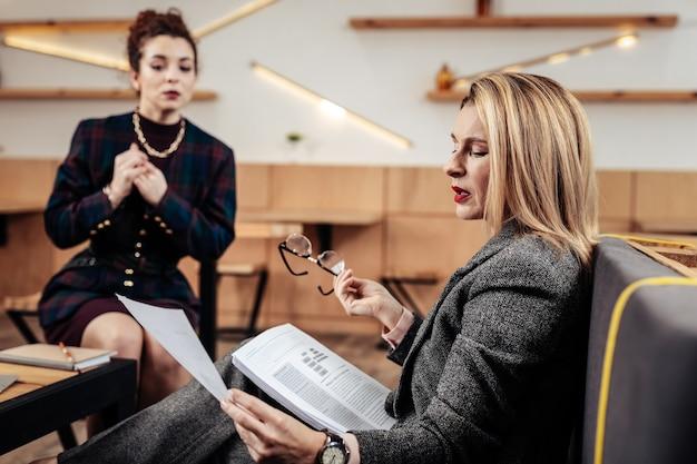 Poser des questions. femme d'affaires élégante aux cheveux blonds posant des questions tout en parlant à sa secrétaire