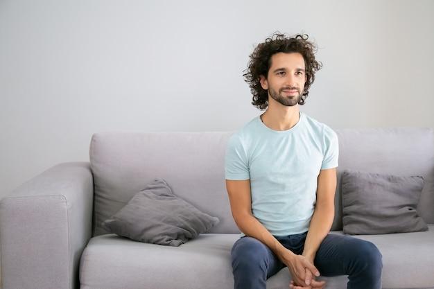 Positif beau mec aux cheveux noirs portant un t-shirt décontracté, assis sur un canapé à la maison, regardant ailleurs et souriant. copiez l'espace. concept de portrait masculin