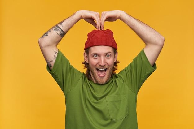 Positif, beau mec barbu aux cheveux blonds. porter un t-shirt vert et un bonnet rouge. a des tatouages. faire signe de coeur avec les mains au-dessus de sa tête. isolé sur mur jaune