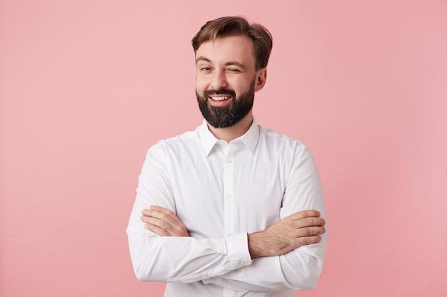 Positif beau mec barbu aux cheveux bruns courts clignotant joyeusement à l'avant tout en posant sur un mur rose, croisant les mains sur sa poitrine, vêtu d'une chemise blanche