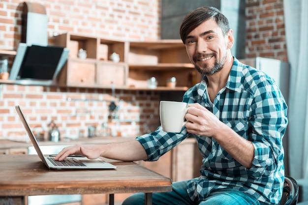 Positif heureux agréable assis dans la cuisine et souriant tout en profitant de son thé