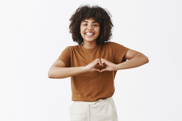 Positif et heureux séduisante femme à la peau sombre avec une coiffure afro montrant le signe du cœur sur la poitrine et souriant avec joie et soin ayant de l'affection ou exprimant son amour sur un mur gris