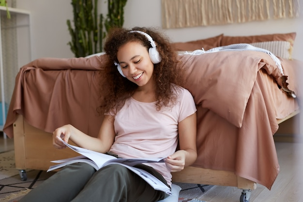 Positif jeune femme afro-américaine aux cheveux bouclés dans la chambre, lisant un nouveau magazine et appréciant sa chanson préférée dans les écouteurs, souriant et regarde.