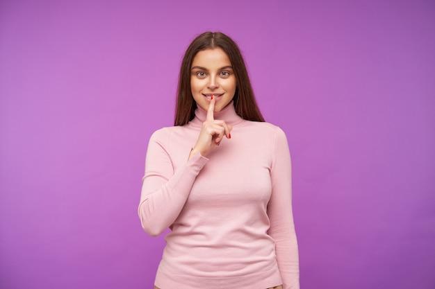 Positif jeune femme aux cheveux bruns aux yeux verts vêtue d'un pull rose à col roulé en gardant l'index sur ses kips tout en souriant agréablement à l'avant, posant sur un mur violet