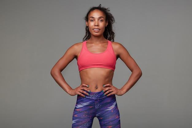 Positif jeune femme brune frisée à la peau foncée active avec piercing au nombril regardant gaiement en se tenant debout. concept de remise en forme et de sport