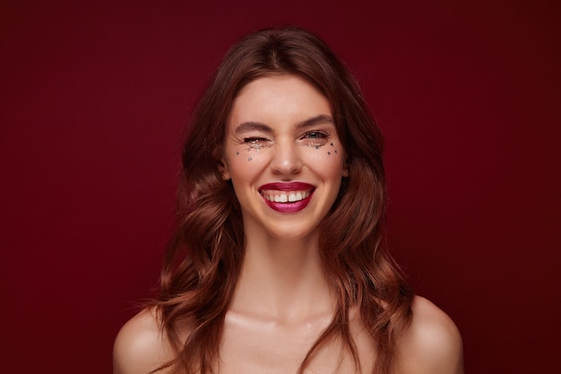 Positif jeune femme brune séduisante avec une coiffure ondulée portant du maquillage de soirée tout en posant, regardant gaiement et en clignant de l'œil