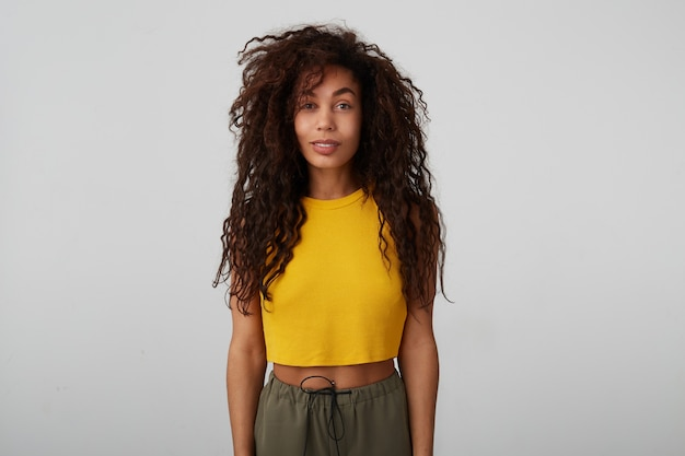 Positif jeune femme brune séduisante à la peau sombre avec des cheveux bouclés sauvages gardant les mains le long du corps tout en posant sur fond blanc dans des vêtements décontractés