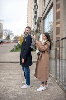 Positif jeune femme debout derrière son mari tout en zippant son sac