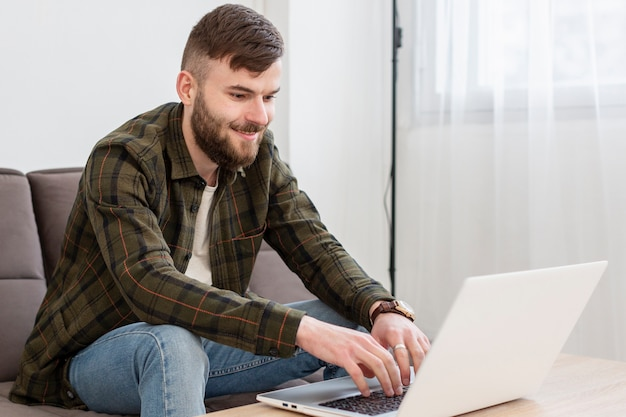 Positif jeune homme appréciant le travail à domicile