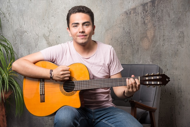 Positif jeune homme assis sur une chaise et jouant de la guitare.