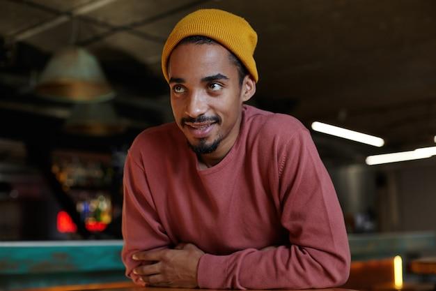 Positif jeune homme barbu à la peau foncée assis à table au-dessus de l'intérieur du bar, gardant les mains jointes et regardant vers l'avant avec un sourire léger, vêtu d'un pull rose et d'une casquette moutarde
