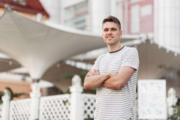 Positif jeune homme mignon avec un beau sourire dans un t-shirt rayé à la mode est debout dans la rue de la ville.