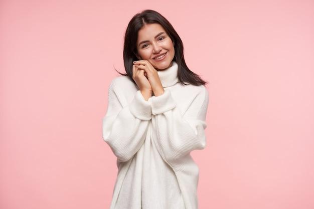 Positif jeune jolie dame aux cheveux bruns avec maquillage naturel soulevant son visage mains jointes et regardant volontiers à l'avant avec un beau sourire, debout sur un mur rose