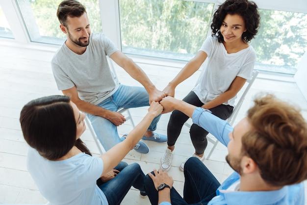 Positif ravi des jeunes assis dans le cercle et souriant tout en mettant leurs poings ensemble
