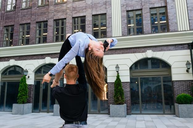 Position d'acro yoga d'un jeune couple, l'homme tient la femme par la jambe et le torse, et la femme parle par smartphone, exercice sur la confiance et le soutien et le concept d'entreprise