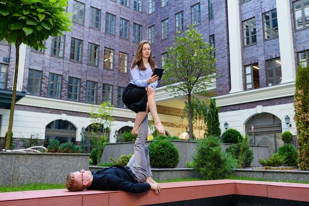 Position d'acroyoga avec une fille assise et en équilibre sur les pieds d'un garçon et regarde l'écran de la tablette, le concept de sport et d'entreprise, le partenariat et le réseau