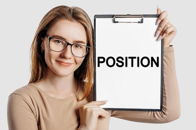 Position. belle jeune femme d'affaires portant des lunettes tient un presse-papiers avec un espace fictif isolé sur fond gris